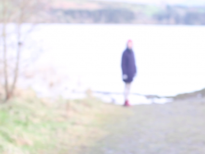 A blurred and washed-out photograph of a person in winter clothes standing by a lake-side